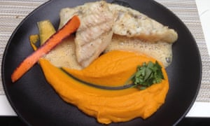 John Dory with carrot mousseline on a black round plate