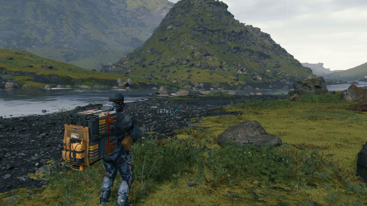 Sam Bridges, a man wearing a large delivery backpack, urinating into some weeds near a river in Death Stranding
