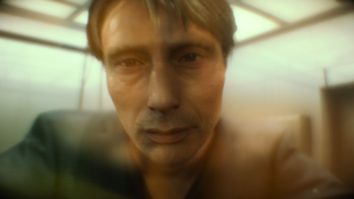 a close-up of a sad-looking man (Mads Mikkelsen) seen through an orange haze in Death Stranding