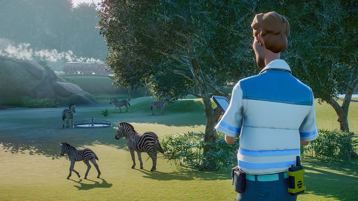a zookeeper watches over zebras in Planet Zoo