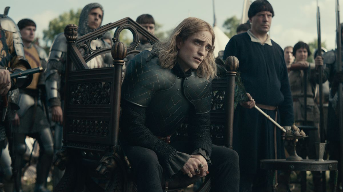 The Dauphin (Pattinson), in armor, sits in a fine chair, surrounded by his soldiers.