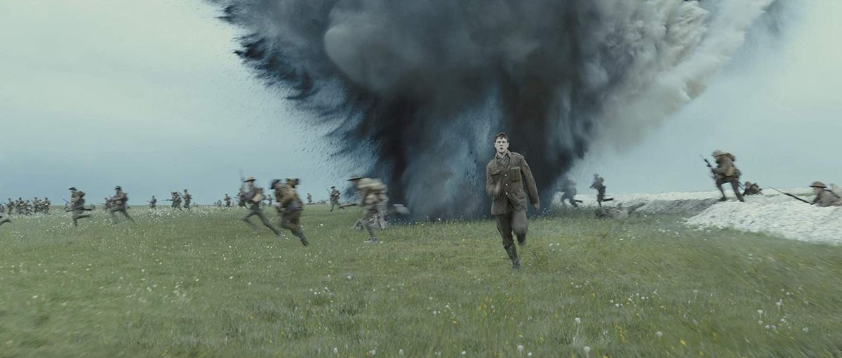 Schofield (George MacKay) runs from German mortar fire across the British trench in 1917