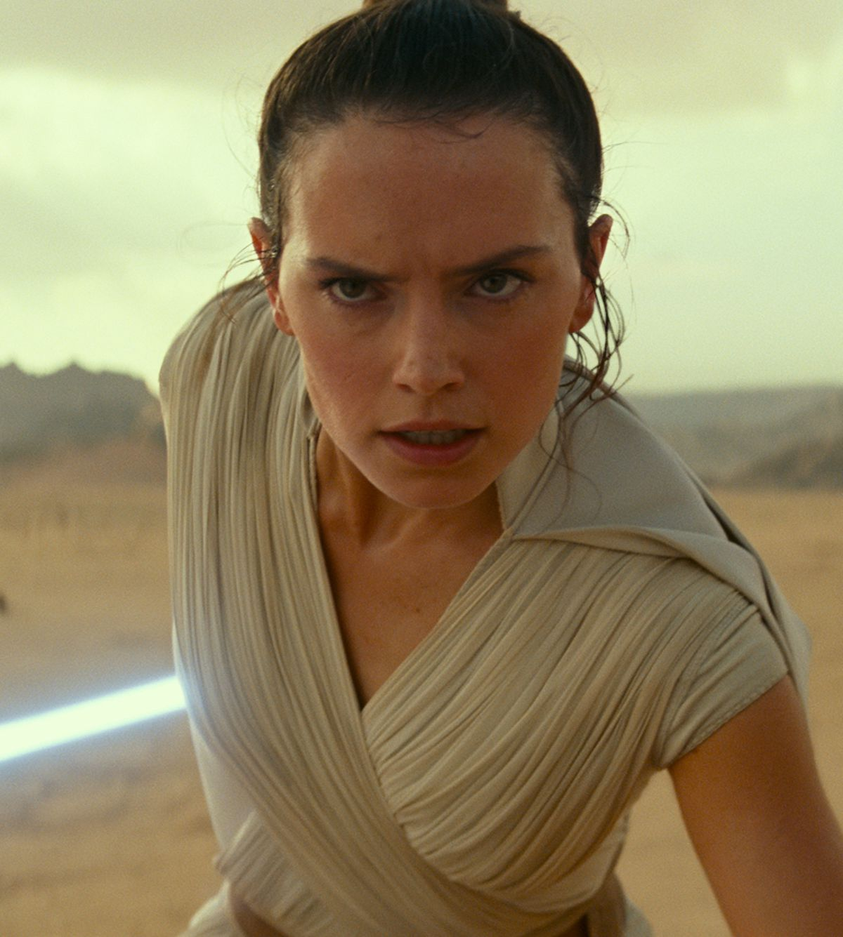 Rey, with lightsaber out, prepares for a fight on a desert planet in Star Wars: The Rise of Skywalker