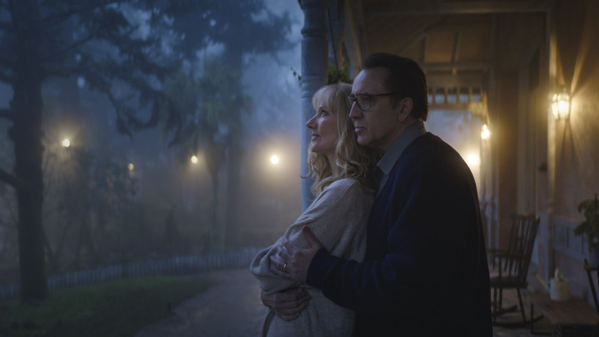 Nicolas Cage embraces Joely Richardson on the front porch of a farmhouse at night in a pastoral setting surrounded by warm light.