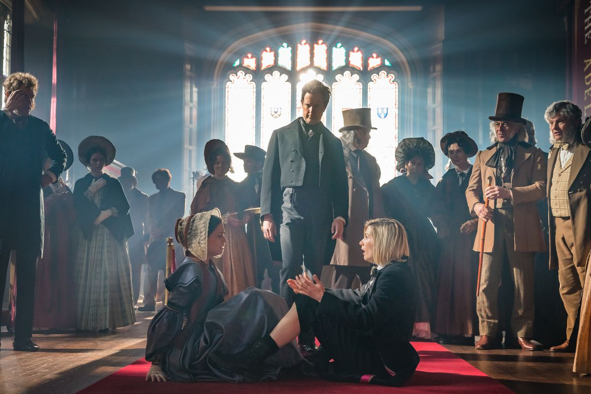 Jodie Whittaker as the Doctor in Doctor Who, sitting on the floor of a room with light streaming in through a stained glass window, surrounded by Ada Lovelace, Charles Babbage and a crowd of curious onlookers.