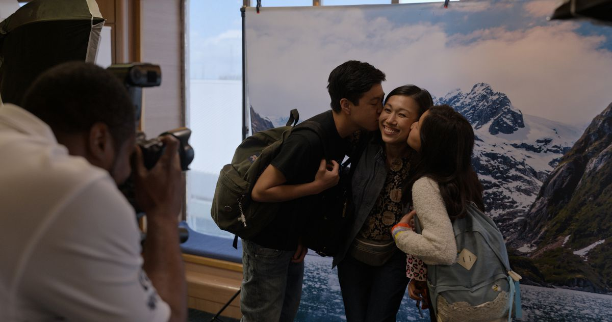 two kids kiss their mother's cheeks as a cameraman takes the photo in Little America