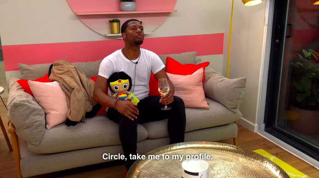 A character on the reality show The Circle holds a stuffed doll, a glass of wine, and asks to see his profile
