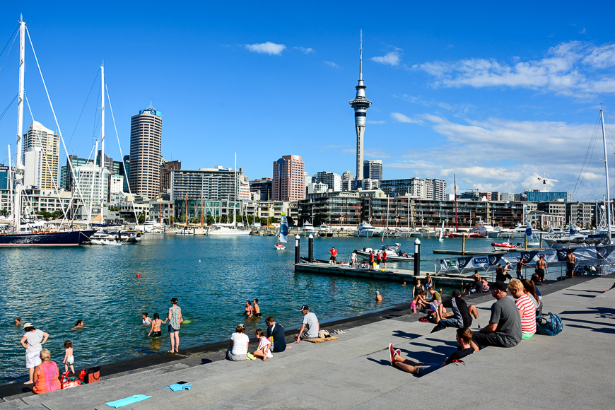 View from the Wynyard Quarter in Auckland, with people, residential and commercial buildings, Sky Tower and boats.