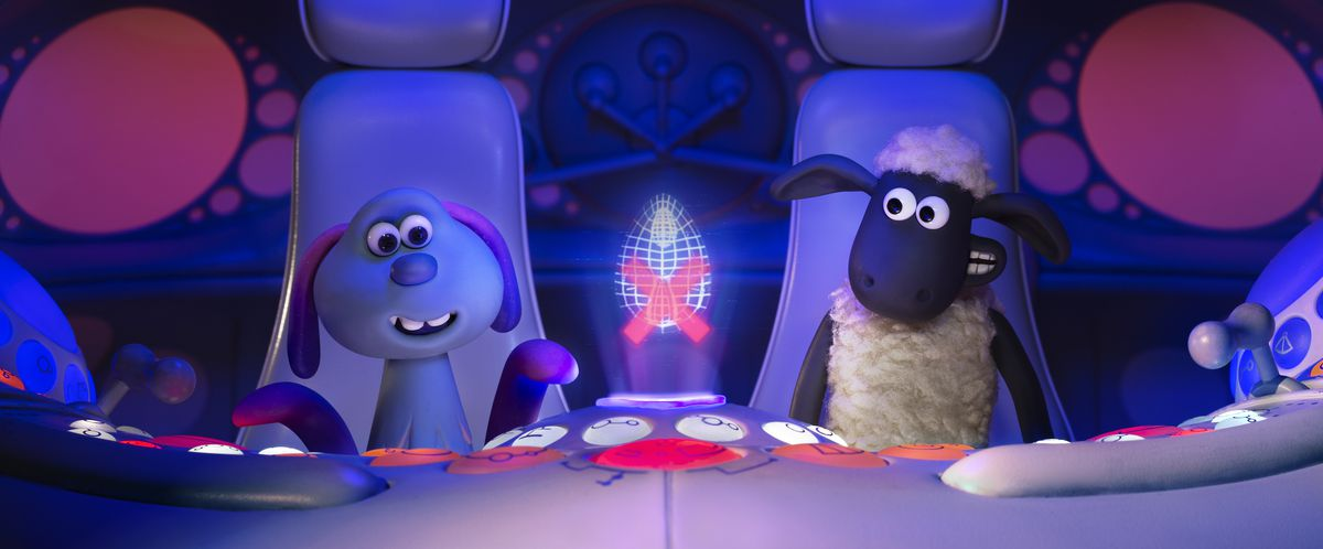 An alien and a sheep sit inside a spaceship.