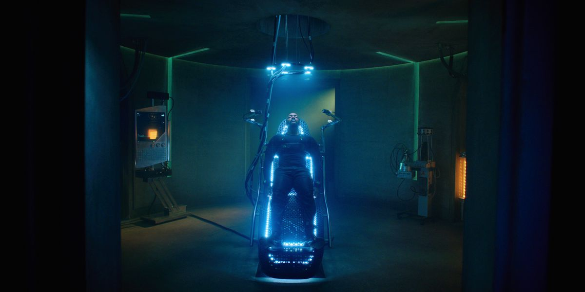 Anthony Mackie lies on a surgical table, wearing a full-body black jumpsuit, lit by blue neon lights built into the table and hanging above him.