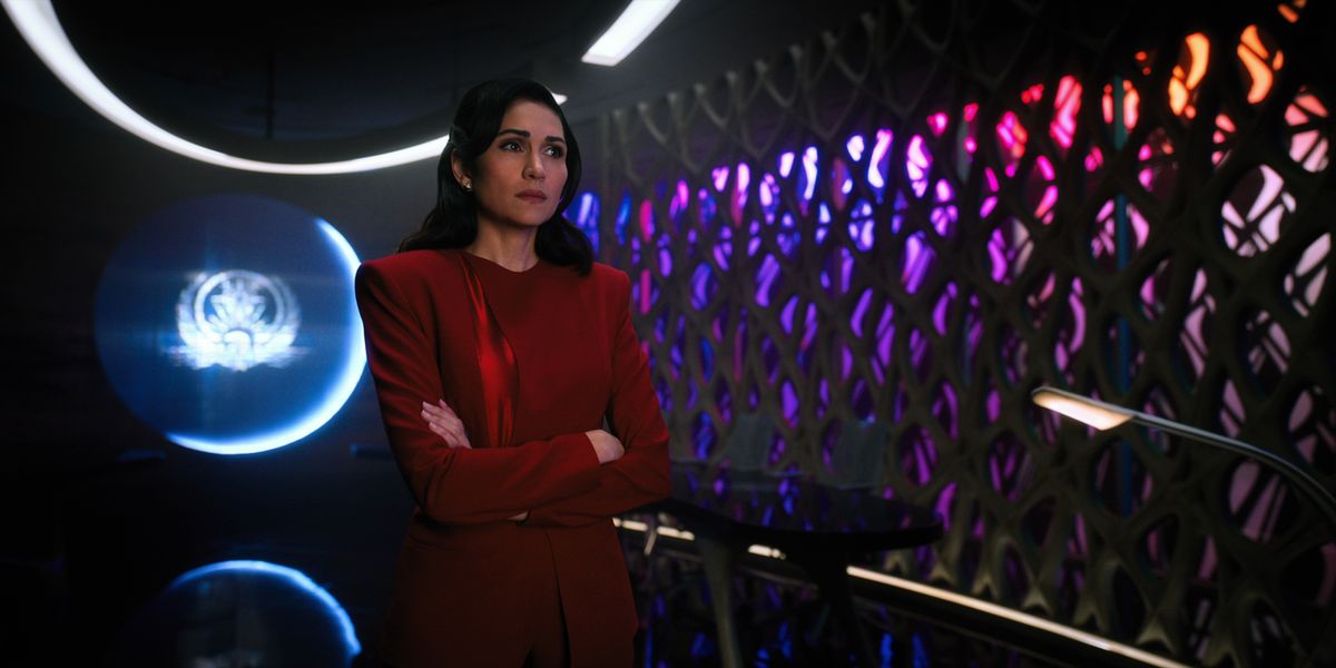 A woman in a blood-red suit stands in a dark room with a sigil glowing in the window behind her, and a bank of multicolored lights shining through cutouts in the wall next to her.
