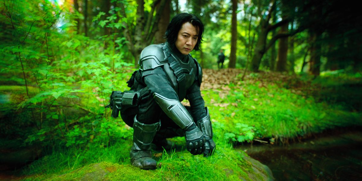An Asian man in matte grey body armor squats by a small body of water in an outdoor setting where the vegetation glows a vivid bright green.