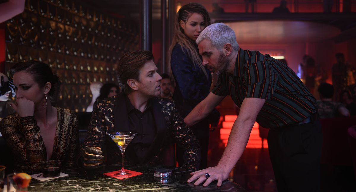 "CHRIS MESSINA as Victor Zsasz leans on a table to talk to a seated EWAN McGREGOR as Roman Sionis, with JURNEE SMOLLETT-BELL as Black Canary in the background, in Warner Bros. Pictures' ""BIRDS OF PREY (AND THE FANTABULOUS EMANCIPATION OF ONE HARLEY QUINN)."