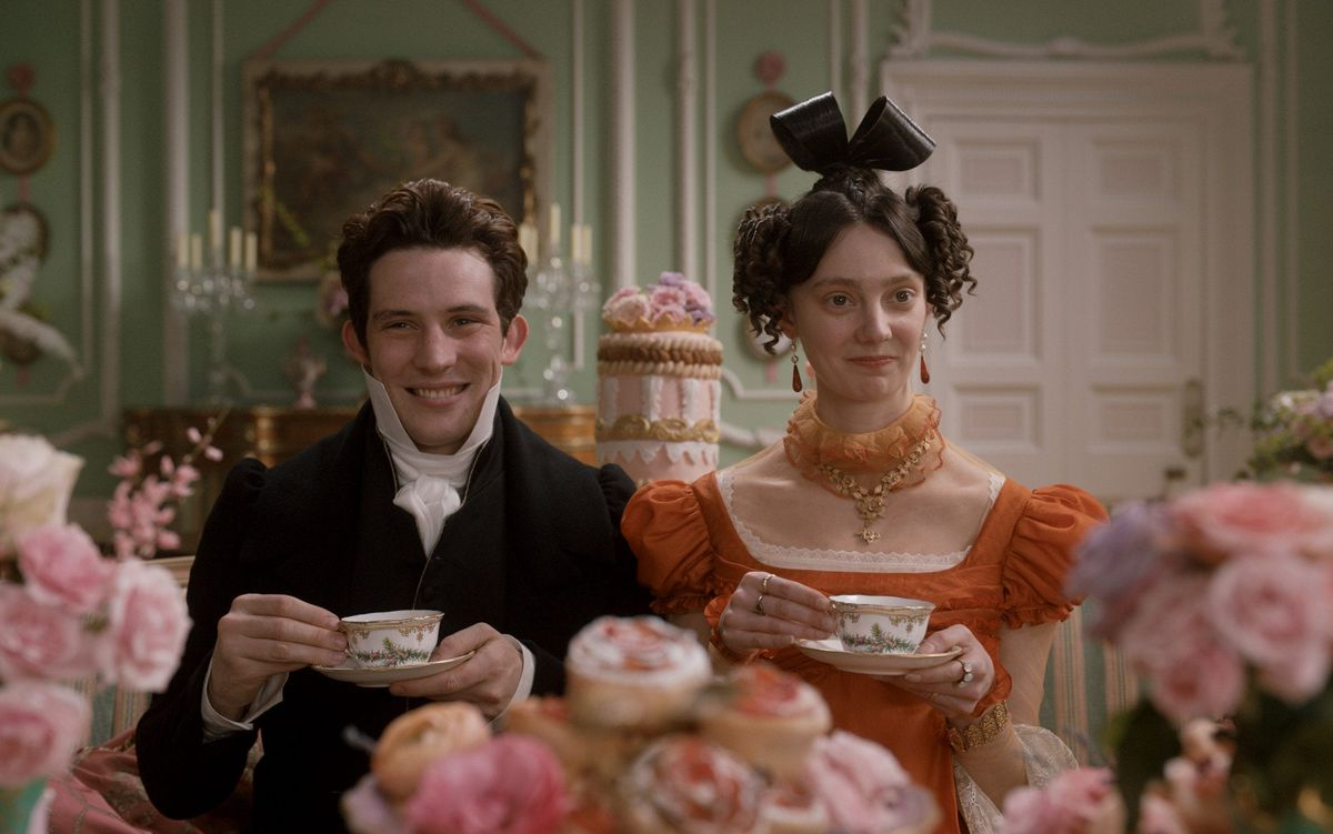 Mr. Elton (Josh O'Connor) and Mrs. Elton (Tanya Reynolds) sit for tea amidst a bunch of flowers.