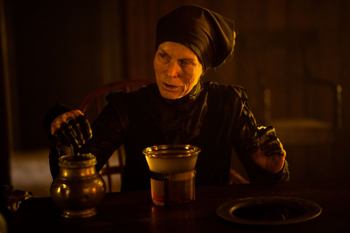 The Witch in Gretel and Hansel, an elderly woman dressed in a black robe and head-wrap, dips her fingers into a black goo.