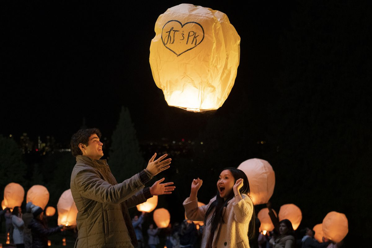 The young couple send a lantern with their initials on it into the air.