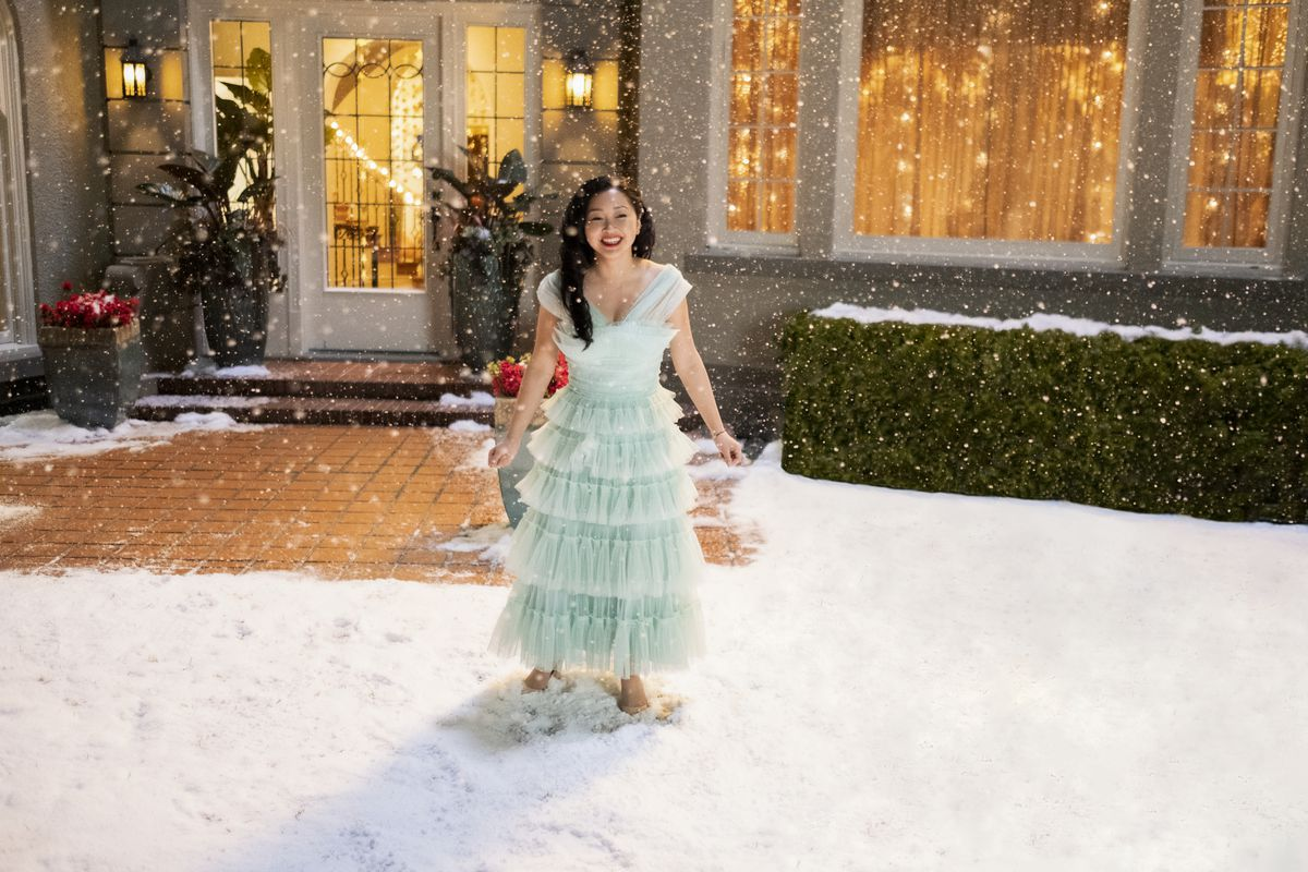 A young woman dressed in a light blue gown stands outside in the snow.