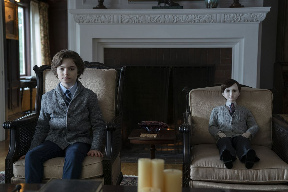 A boy and a porcelain doll sit on near-identical tan chairs, wearing similar grey pullovers, navy slacks, and button-down shirts and ties. They're both staring into the camera in a creepy way.