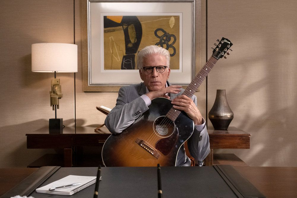 "Michael (Ted Danson) rests his chin on a guitar in a screenshot from The Good Place season 4, episode 13 ""Whenever You're Ready"""