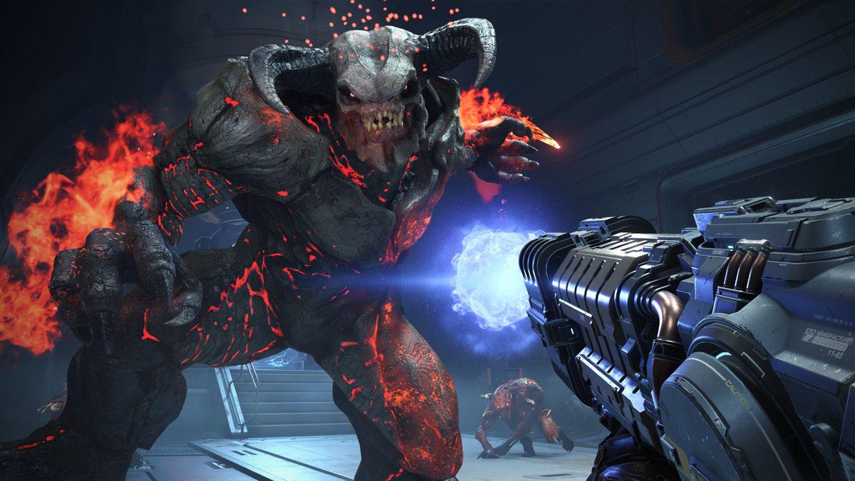 a huge, horned demon covered in flames leers over the player in Doom Eternal