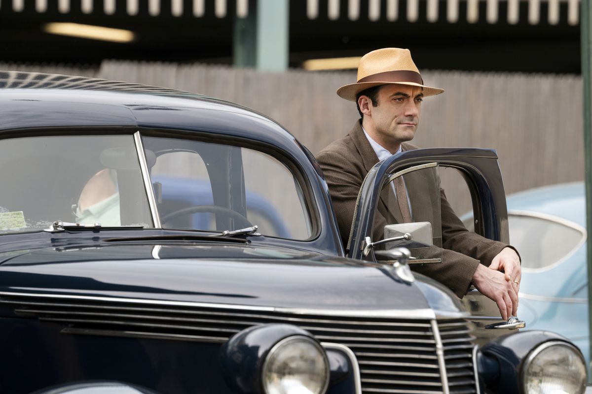 Morgan Spector, wearing a brown suit and tan hat, stands behind the open driver's-side door of a vintage car, hands dangling out through its open window, in a scene from The Plot Against America.