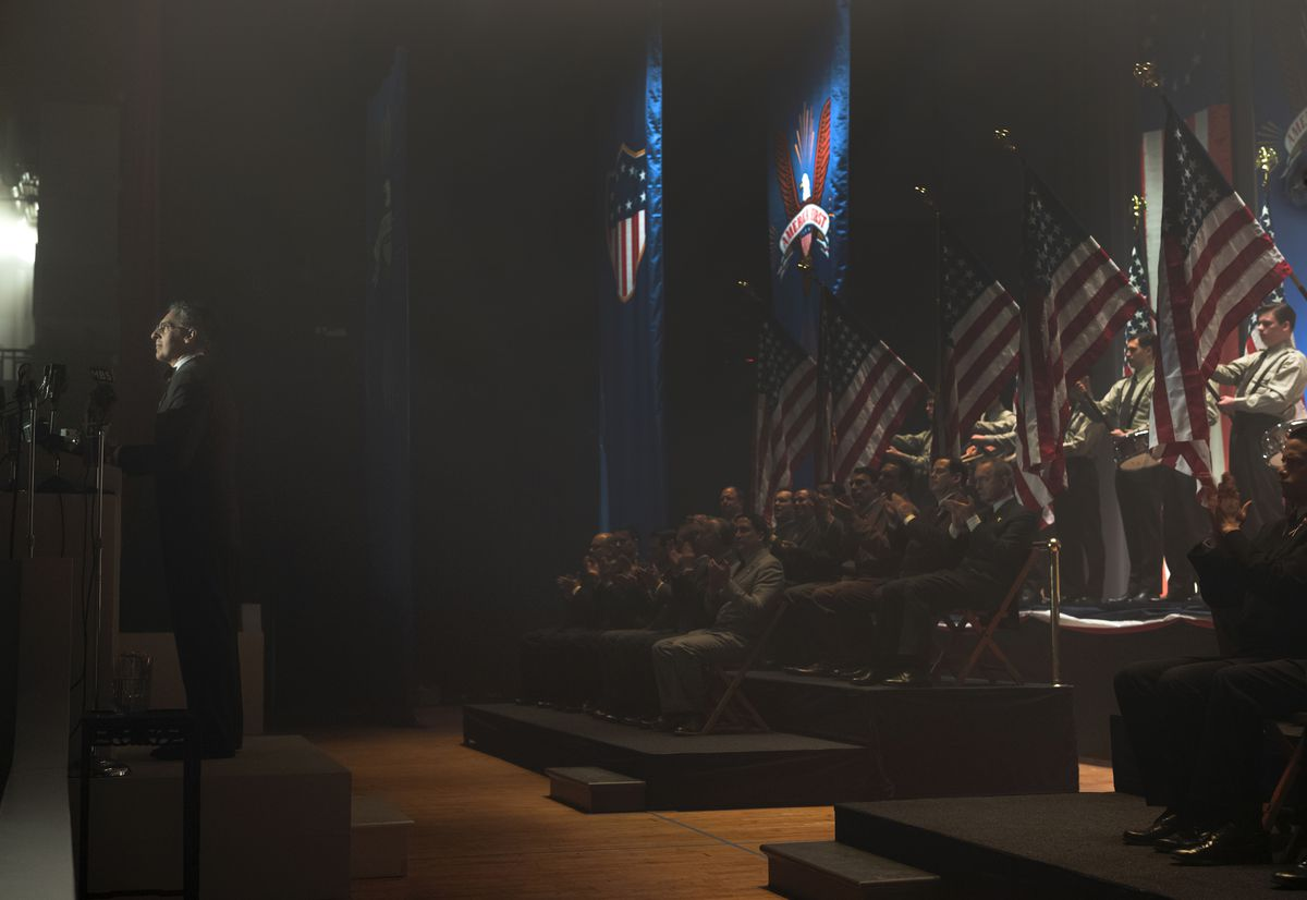 John Turturro, in a dark suit and skullcap, stands at a podium on the extreme left of a dark room, while suited men sitting behind him on the right applaud, and a line of brown-shirted men hold up large American flags behind them.