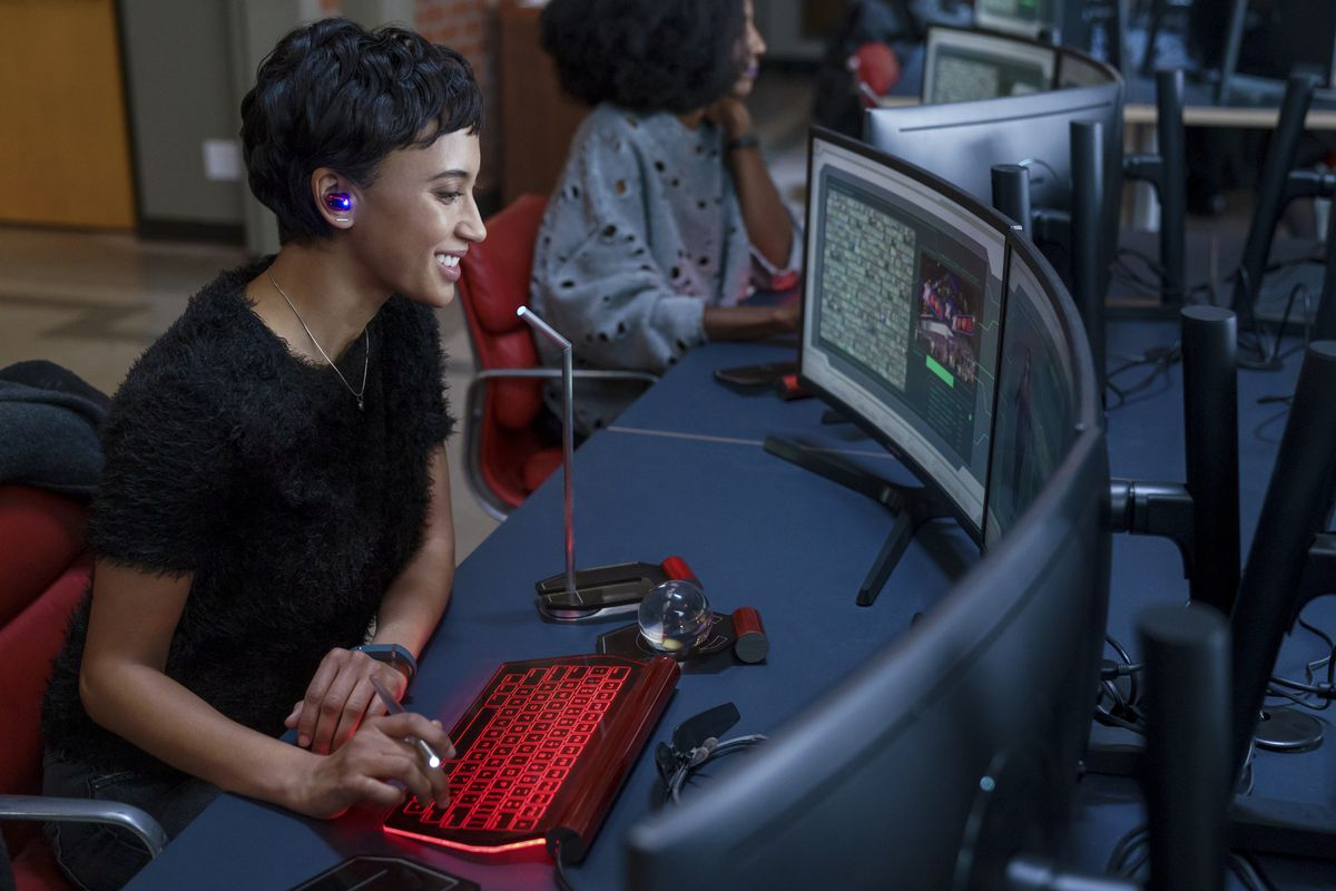 Andy Allo sits at a curved bank of computer monitors with her hands on a bright red keyboard, smiling as she looks at something onscreen.