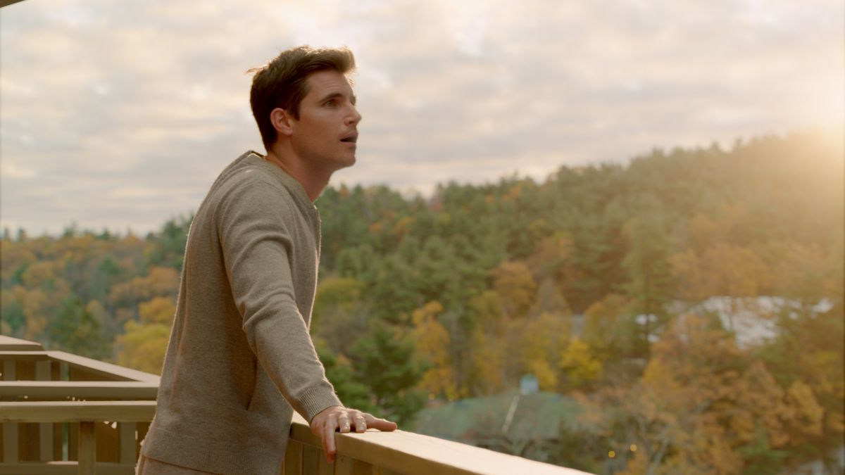Robbie Amell stands on a balcony with his mouth hanging open, looking out on a lush forest glowing with sunlight.