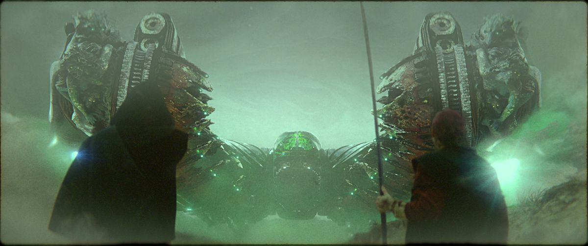 Two black-robed figures, one with a long staff, stand with their backs to the camera, facing a symmetrical spaceship backlit in green