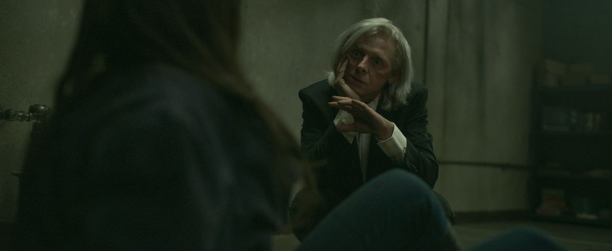 Simon Pegg, in a suit and with long, white hair, sits in a dingy bunker and talks to Lily Collins in Inheritance.