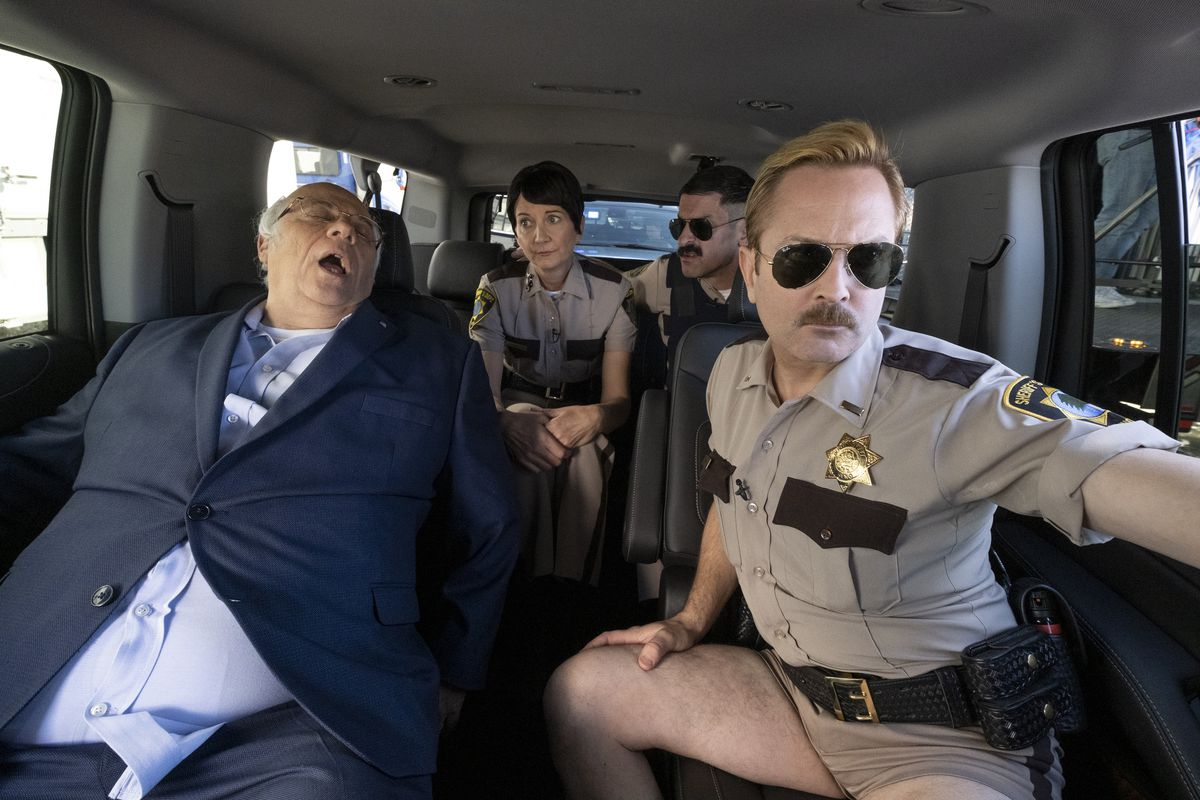 Three members of the Reno 911! sheriff's department ride in the back of a van with a passed-out older man.