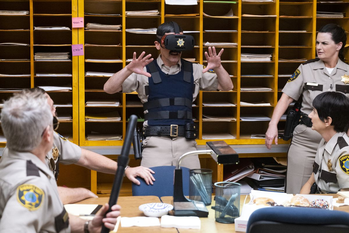 A Reno 911! character in a virtual-reality headset holds up his hands in excitement as other sheriff's department employees watch.