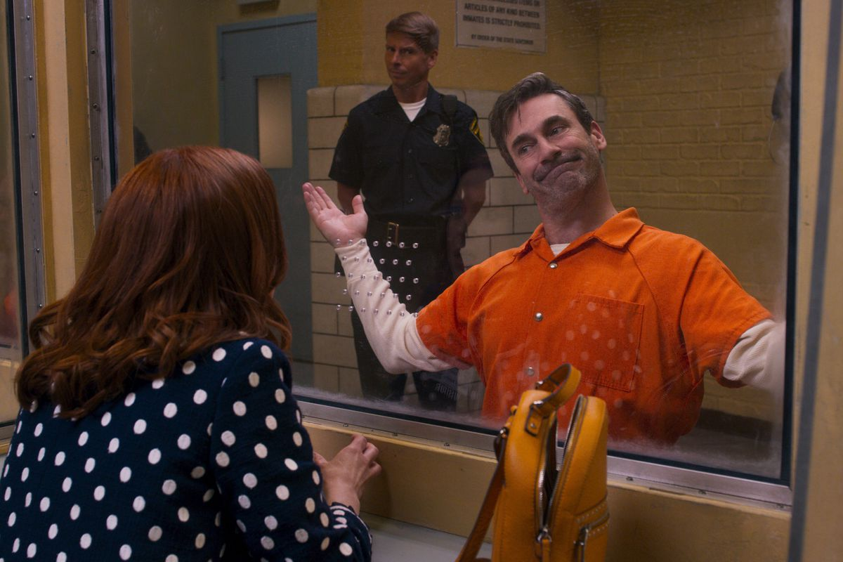 Jon Hamm as the Reverend in Unbreakable Kimmy Schmidt wears an orange prison jumpsuit and shrugs dismissively at Kimmy from the other side of a prison visitation window.