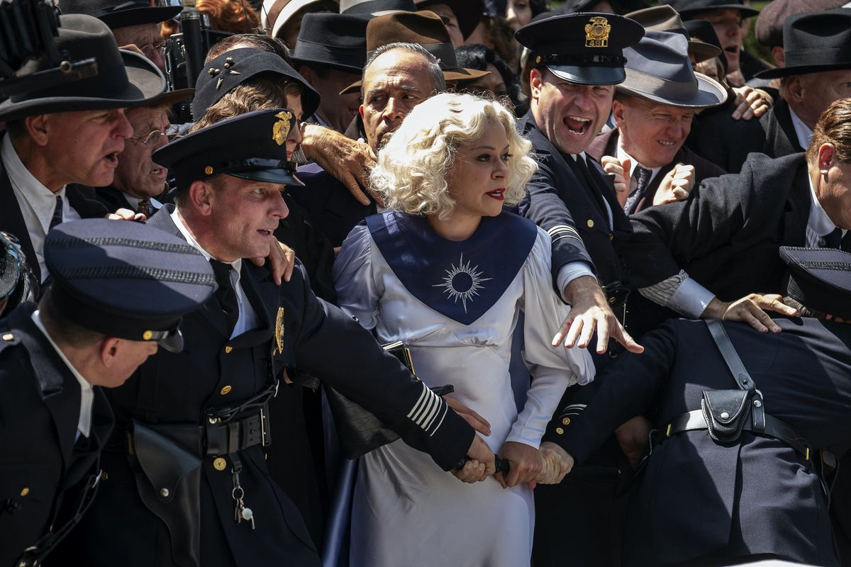 Excited cops surround Tatiana Maslany in HBO's Perry Mason reboot.