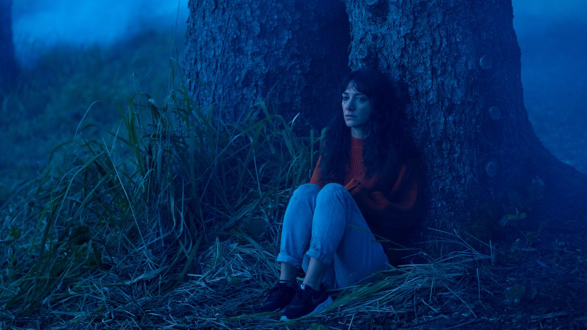 Sheila Vand sits glumly under a tree in Dave Franco's The Rental.