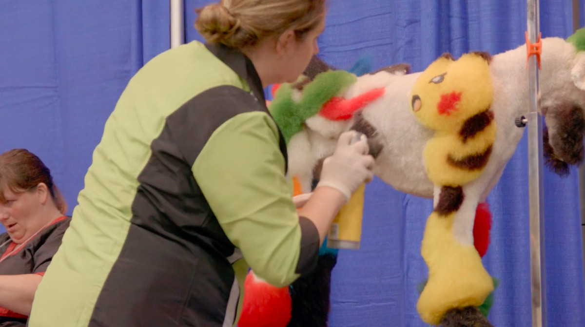 A groomer puts the final touches on a fluffy Pikachu shaved into her dog's fur in the documentary Well Groomed