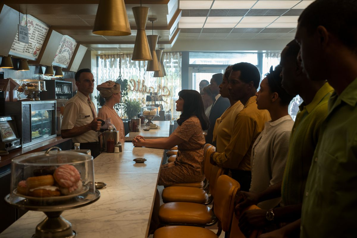 Emmy Raver-Lampman sits at the counter at a 1960s diner with a row of Black men and women standing behind her in season 2 of The Umbrella Academy.