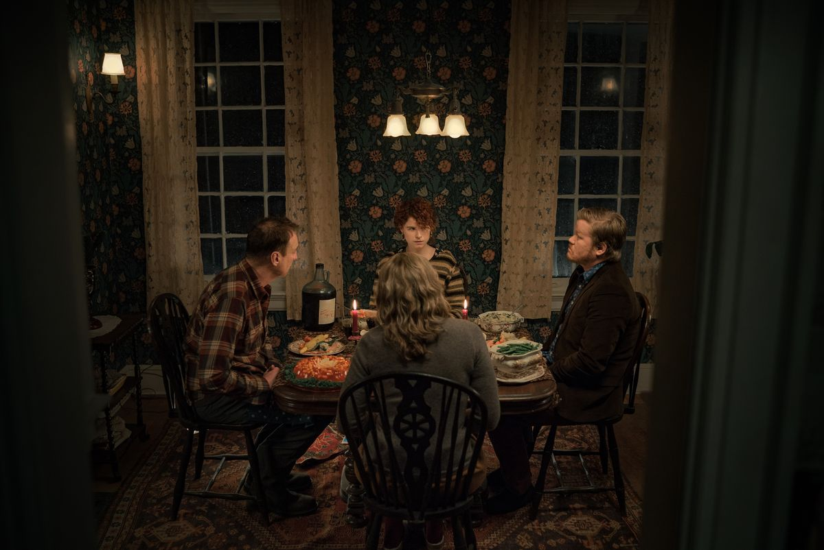 a group sit around a dinner table