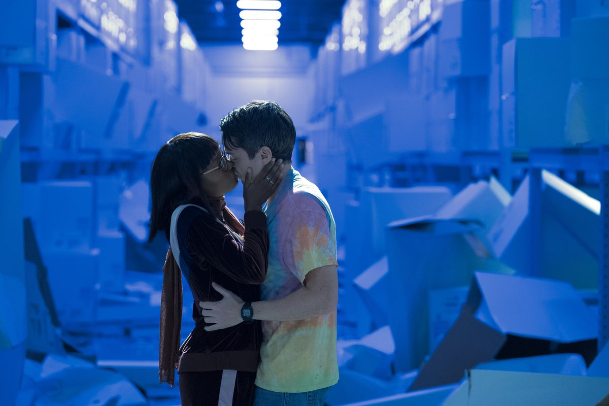 Two characters kiss in front of a deep blue background in Amazon's Utopia