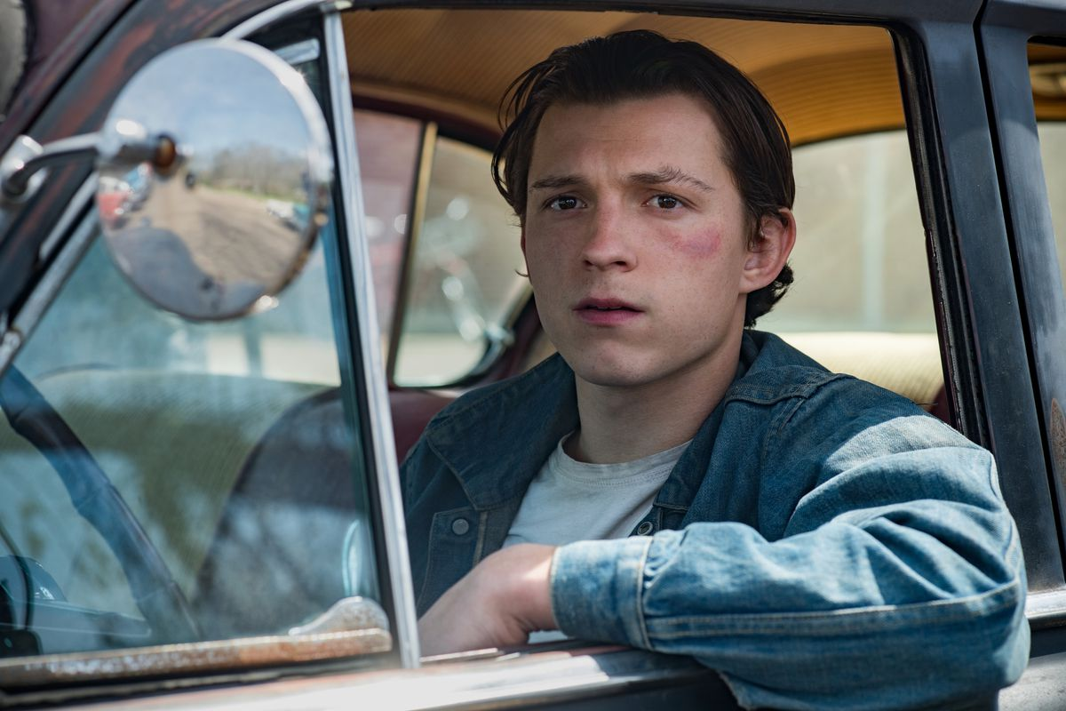 tom holland stares wistfully out the window of a car