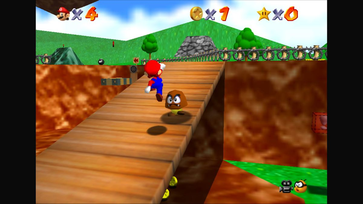 Mario jumps up a ramp, aiming for a goomba, in Super Mario 64