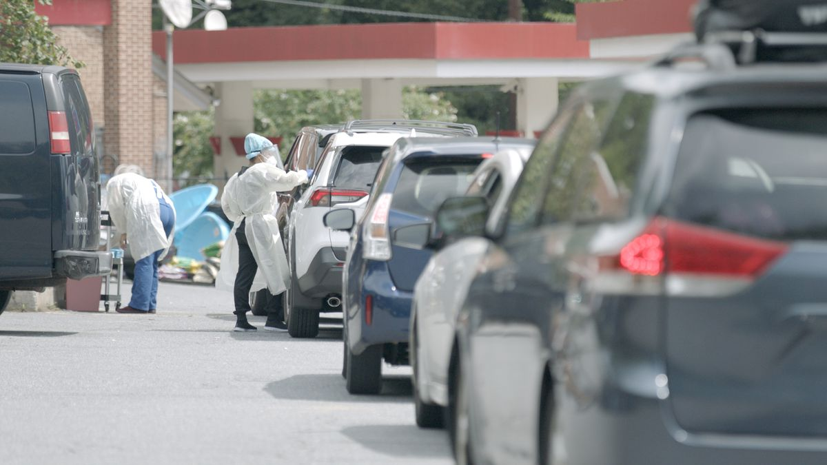 Cars line up for drive-through coronavirus tests in the documentary Totally Under Control