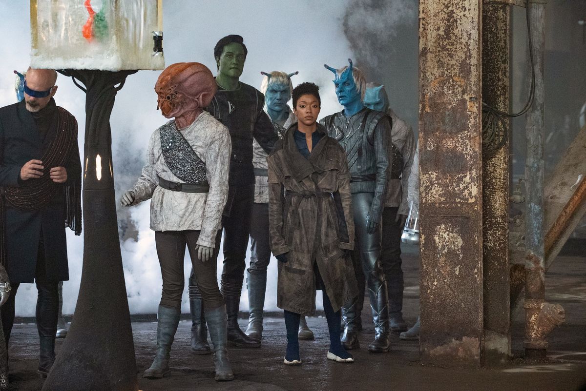 Sonequa Martin-Green as Michael Burnham stands in a group of aliens in Star Trek: Discovery