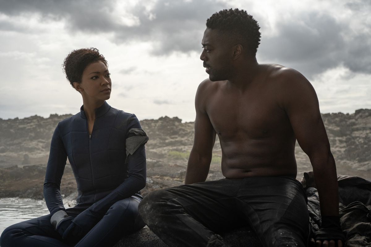 Sonequa Martin-Green sits next to shirtless David Ajala in a barren landscape by water in Star Trek: Discovery