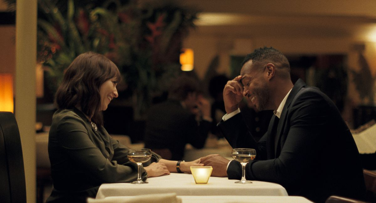 Rashida Jones and Marlon Wayans sit in a restaurant laughing together in On the Rocks
