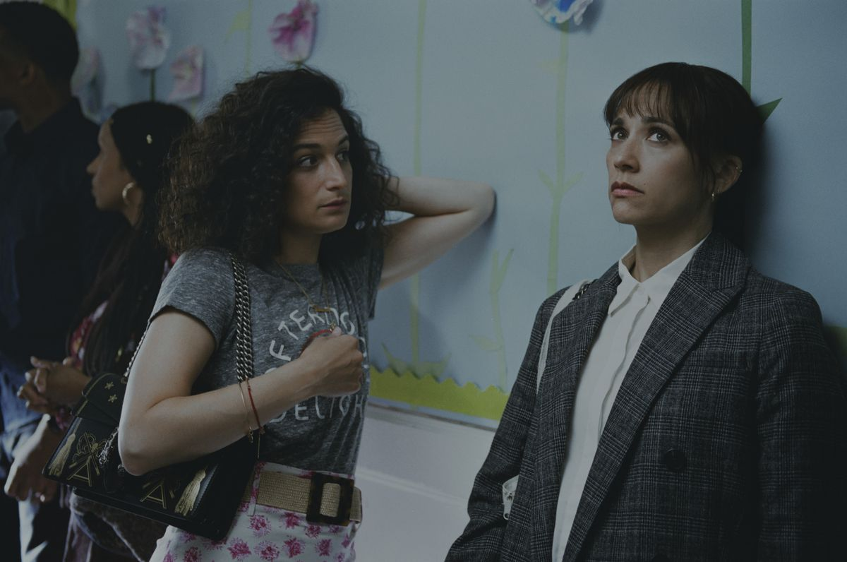Jenny Slate, looking curious, leans against a wall with Rashida Jones, looking exasperated, in On the Rocks