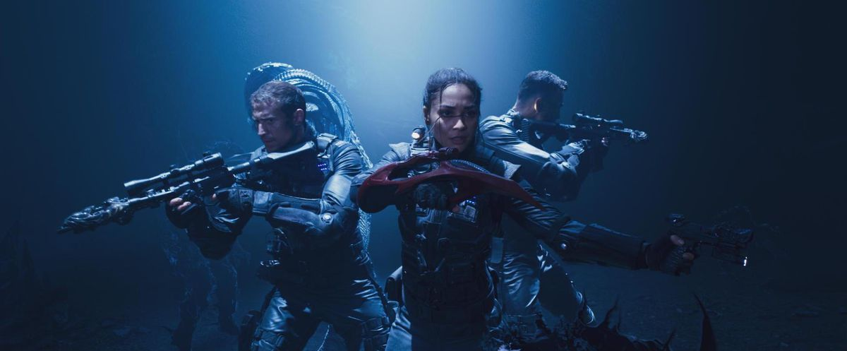 Lindsey Morgan and her co-stars in military gear, under blue light, waving their guns threateningly