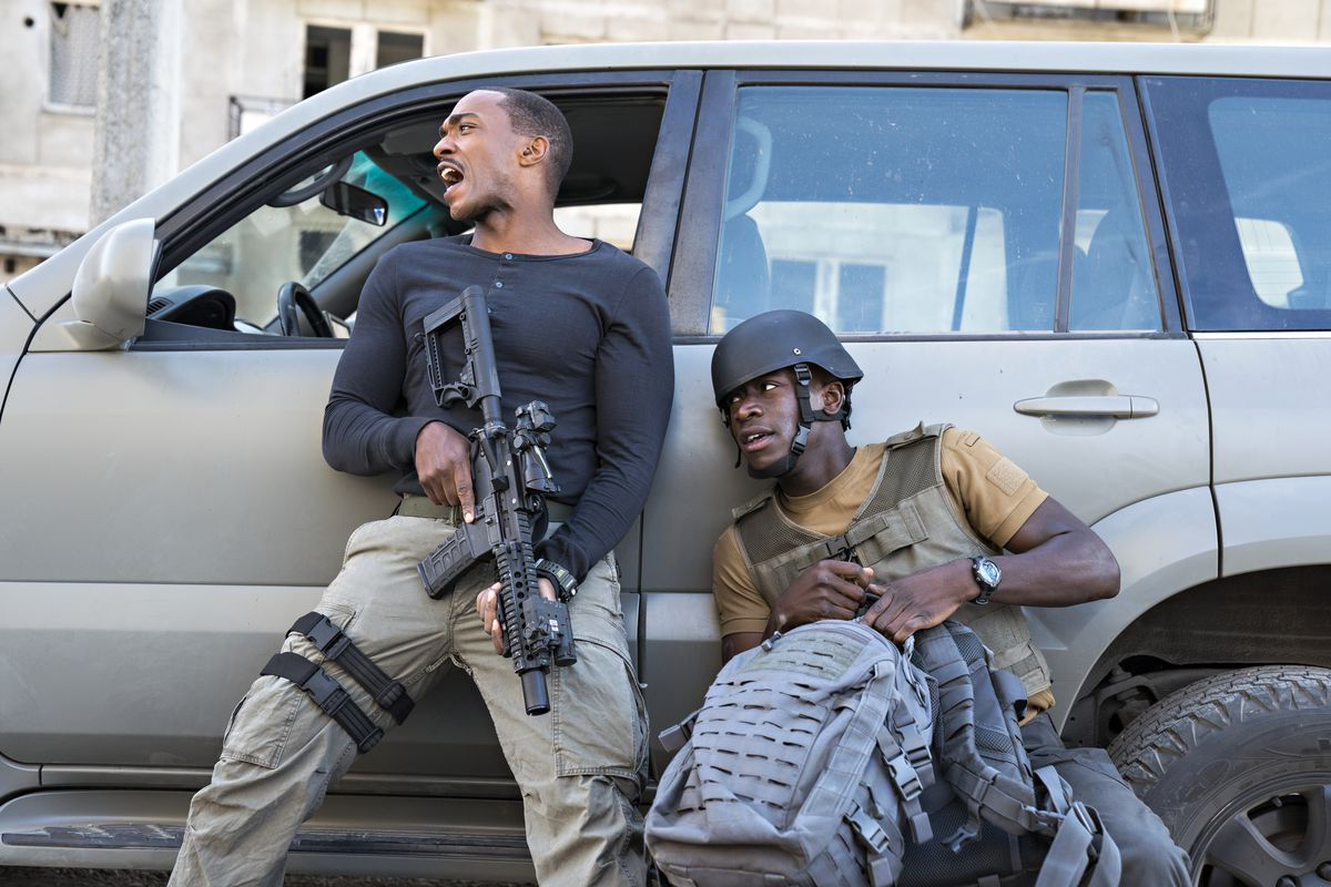 Damson Idris and Anthony Mackie take shelter behind a car in an action sequence in Outside the Wire