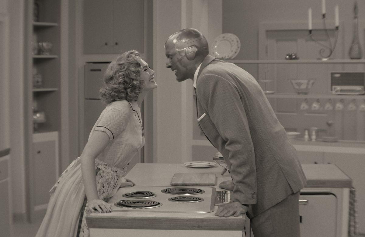 Wanda and Vision lean over the kitchen island to make kissy faces at each other in WandaVision