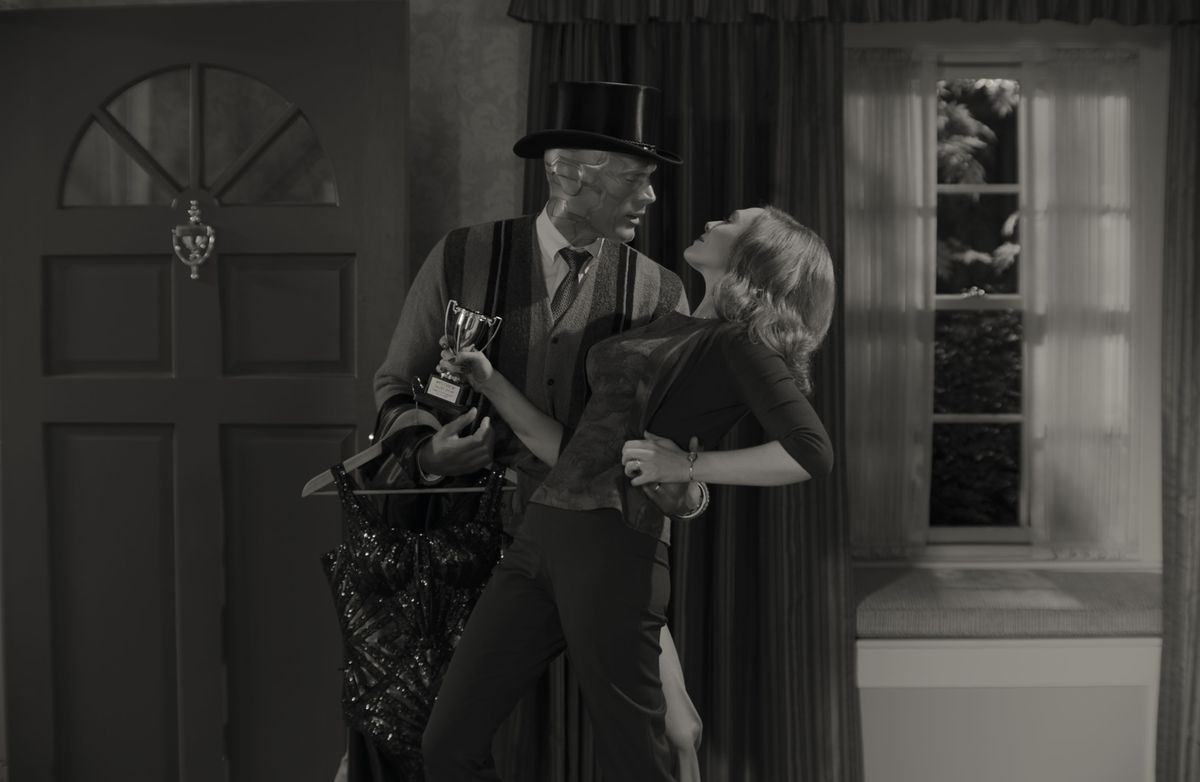 Vision wears a magician's hat as he dips Wanda at the front door of their house in wandavision